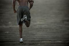 Black man running up stairs Stock Photos