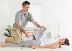 Chiropractor stretching young woman's leg - stock photo
