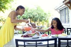 African American woman serving juice to daughter Stock Photos