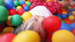 three year old boy in a pool of coloured balls - stock footage