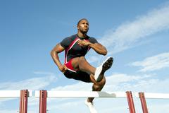 Black runner jumping hurdles in track race Stock Photos