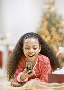 Mixed race girl holding cell phone on christmas Stock Photos