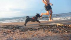Funny Man and Dog Running Beach - stock footage