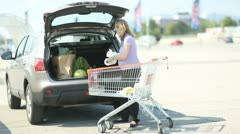 Expecting mother putting daily shopping in car Stock Footage