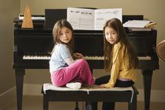 Asian sisters sitting at piano Stock Photos