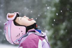 Asian girl sticking out tongue in snow Stock Photos