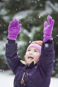 asian girl with arms raised in snow - stock photo