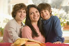 hispanic mother and sons next to plate of cookies - stock photo