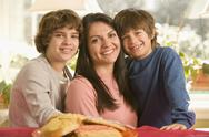 Stock Photo of hispanic mother and sons next to plate of cookies