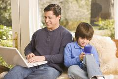 hispanic father and son relaxing - stock photo