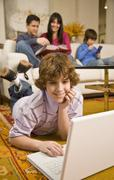 Hispanic boy looking at laptop with family in background Stock Photos