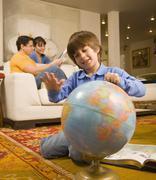 Hispanic boy spinning globe Stock Photos