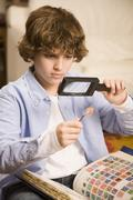 Stock Photo of hispanic boy examining stamp through magnifying glass