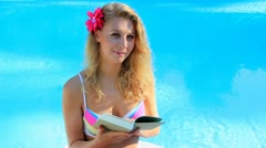 Woman in holidays reading a book Stock Footage
