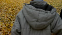 Grandmother and two grandsons walking over carpet of leaves Stock Footage