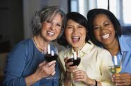 Multi-ethnic women drinking wine Stock Photos