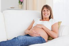 Good looking pregnant woman posing while lying on a sofa - stock photo
