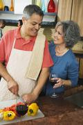 Woman smiling at husband chopping vegetables Stock Photos