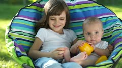Happy kids outdoors. The elder sister kissing younger brother Stock Footage