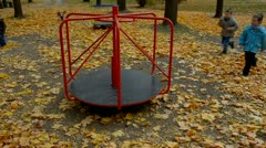 Kids on playground, approaching and starting rotation of carousel Stock Footage