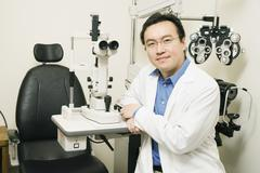Asian male optometrist in office Stock Photos