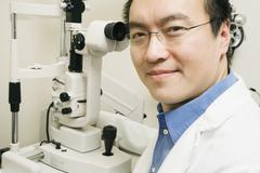 Asian male optometrist with equipment Stock Photos