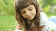 Closeup portrait girl with magnifier lying on the grass Stock Footage