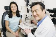 Asian male optometrist examining patient Stock Photos