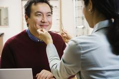 Asian man trying on eyeglasses Stock Photos