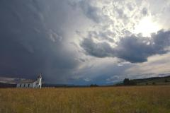 country church with storm clouds - stock photo