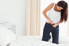 brunette woman kneeing on bed trying to close her jeans - stock photo