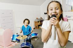 Asian sisters playing drums and singing Stock Photos