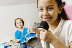 asian sisters playing drums and singing - stock photo