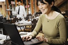 asian businesswoman typing on laptop - stock photo