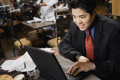 asian businessman typing on laptop - stock photo