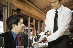 asian waiter showing wine to customer - stock photo