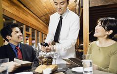 asian waiter pouring wine for customers - stock photo