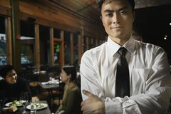 asian waiter with arms crossed - stock photo