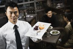 asian waiter carrying plate of food - stock photo