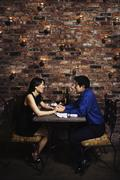 Asian couple holding hands at restaurant Stock Photos