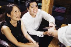 asian couple paying restaurant bill - stock photo