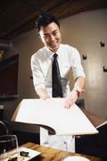 asian waiter pointing to menu - stock photo