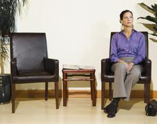 Mixed race woman sitting in waiting area Stock Photos