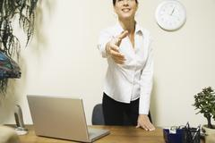 mixed race businesswoman offering hand to shake - stock photo