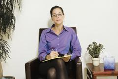 Mixed race female psychiatrist holding notepad Stock Photos