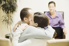 Stock Photo of multi-ethnic couple hugging at therapy session