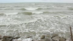 Big waves and heavy wind hit the rock beach Stock Footage