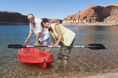 Stock Photo of multi-ethnic senior couple next to kayak in water