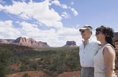 multi-ethnic senior couple looking at desert landscape - stock photo