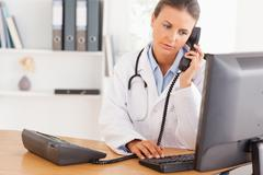 Serious doctor on the phone Stock Photos